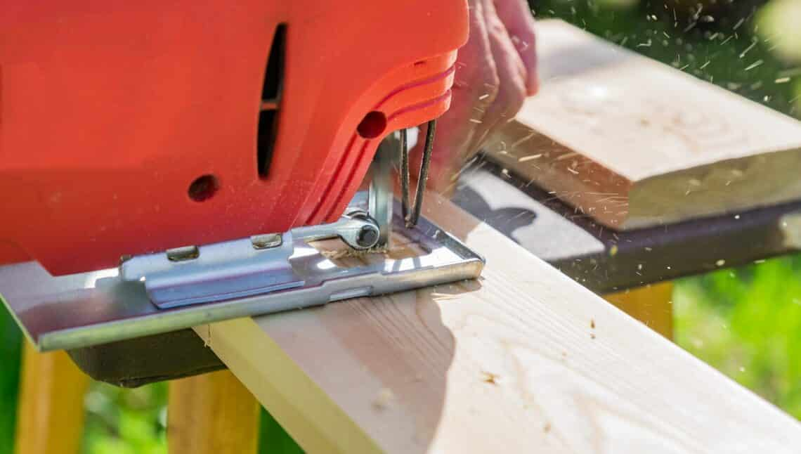wood worker cutting wooden panel with jig saw outdoors, Close-up view of man working with electric jigsaw and wooden plank