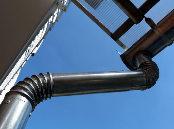 闪亮的新,新安装的镀锌防锈钢屋檐玻璃雨棚边缘和雨水leader和落水管在蓝天下